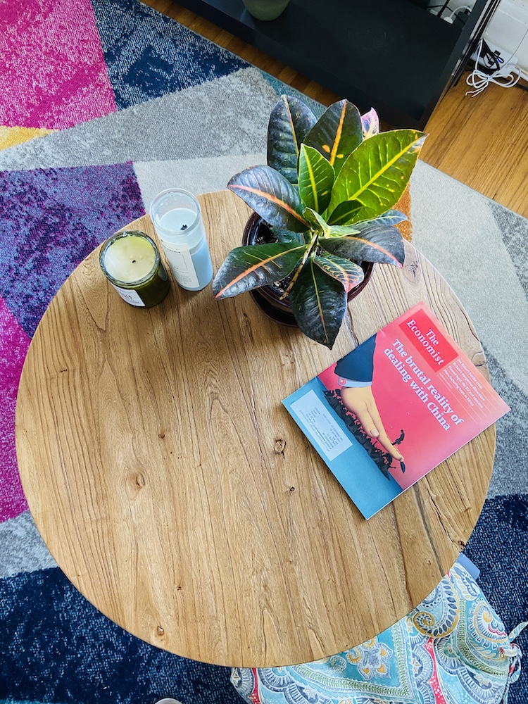Bohemian coffee table with a plant, magazine, and candles and a colorful rug underneath
