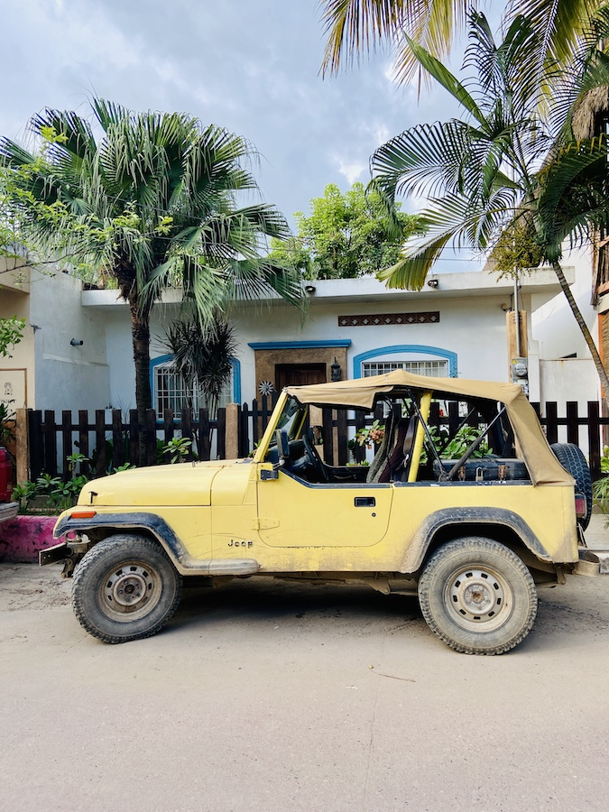 Yellow jeep in front of small casa in San Pancho